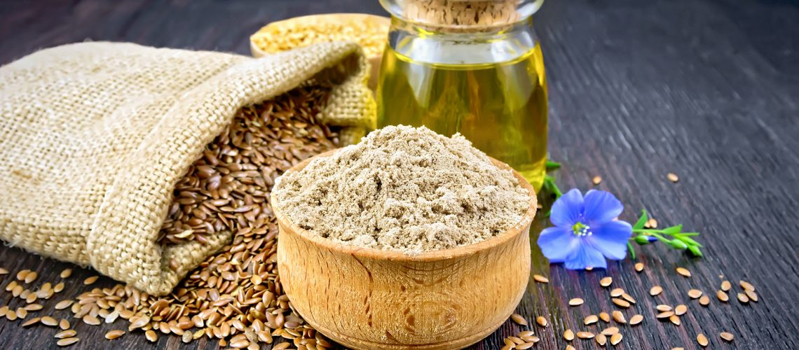 Flax flour in a bowl, seeds in a bag and on a table, blue linen flower and oil in a glass jar on a wooden board background